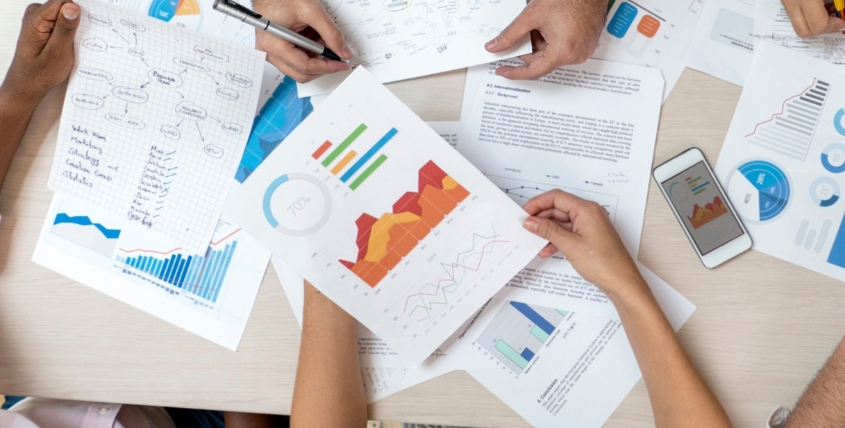 Overhead image of charts and graphs on paper, printed in color